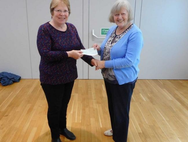 Mary Clarke receives the cheque from Anne Hay.