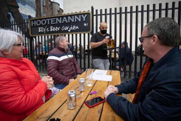 Central Fife Times: Members of the public enjoy their first drink in a beer garden at the Hootenanny, Glasgow.