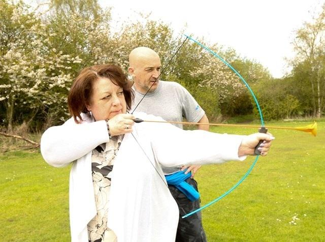 Linda Erskine tries archery at the park.